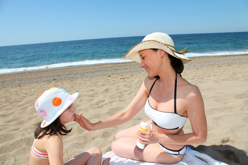 mãe cuidando da pele da criança no verão